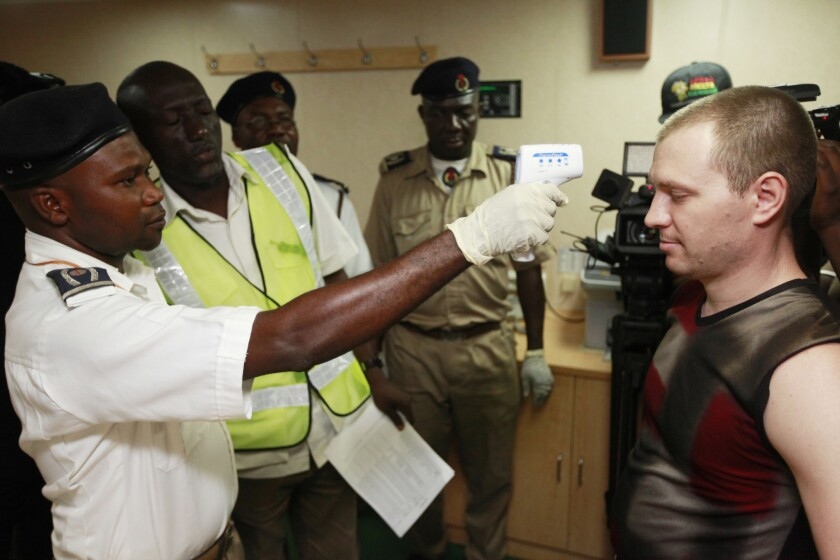 A Nigerian port health official, left, uses a thermometer to screen an unidentified Ukrainian crew member, right, for Ebola on the deck of a cargo ship at the Apapa port in Lagos, Nigeria.