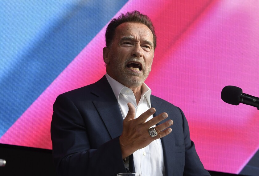 Arnold Schwarzenegger, in jacket and open-collar shirt, gestures while speaking into a microphone.