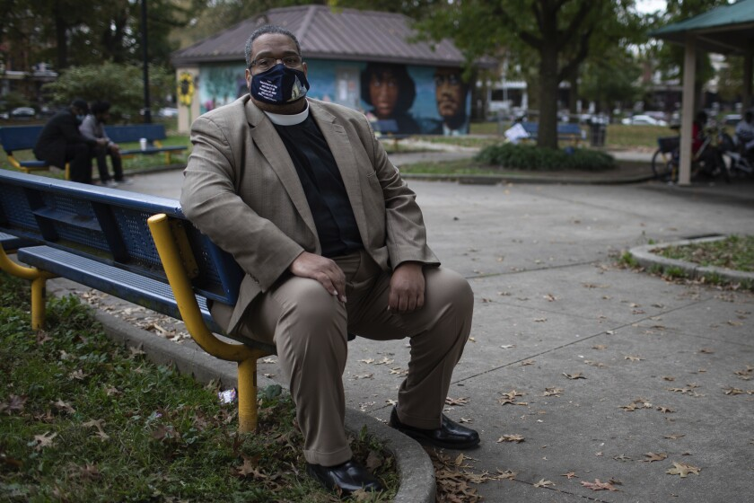 Bishop Duane Royster sits on a bench in a park in Philadelphia