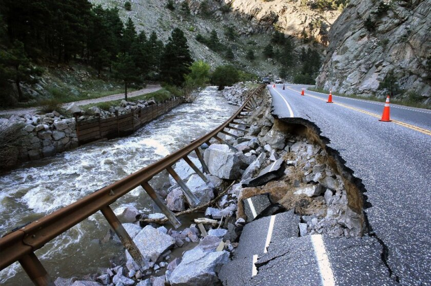 A guardrail hangs away from a flood-damaged canyon road, which links Boulder with the mountain town of Nederland.
