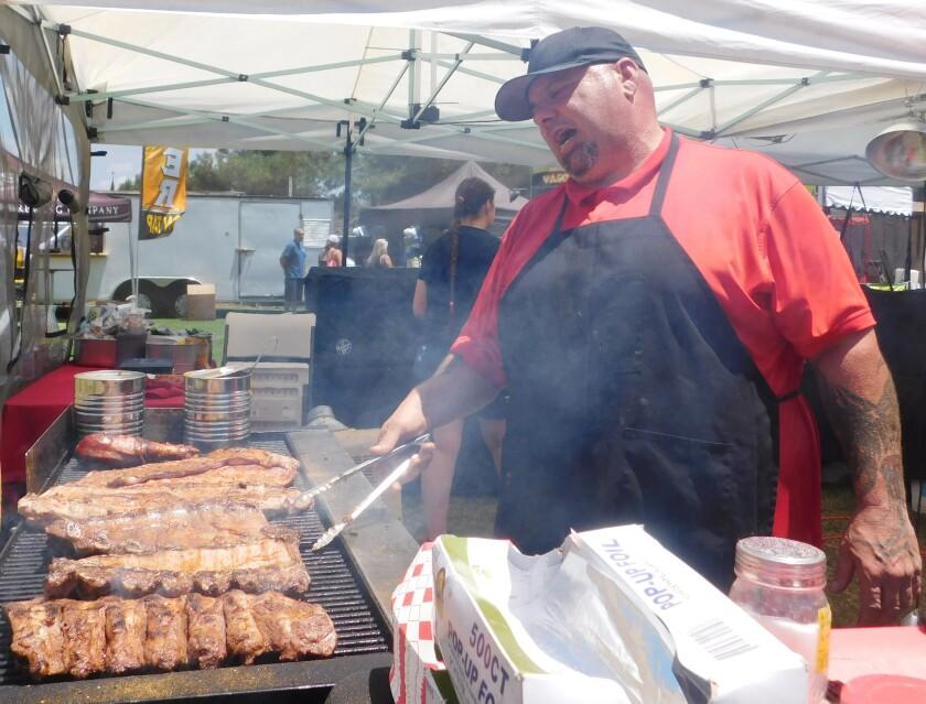 Ο ιδιοκτήτης του Meat Monsters Grill Anthony Andrews ετοιμάζει ένα γλέντι στη σχάρα στον πάγκο φαγητού του.