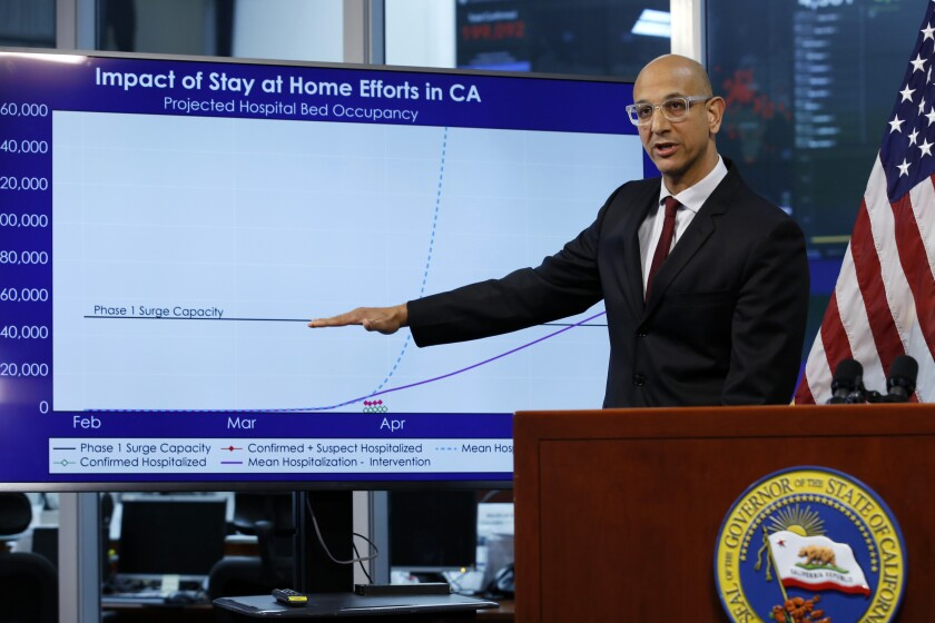 """FILE - In this April 1, 2020, file photo Dr. Mark Ghaly, secretary of the California Health and Human Services, gestures to a chart showing the impact of the mandatory stay-at-home orders during a news conference on the state's response to the coronavirus, at the Governor's Office of Emergency Services in Rancho Cordova, Calif. Ghaly said Thursday, June 4, 2020, the state is staying in a """"range of stability"""" on coronavirus cases and hospitalizations and has no plans to scale back its reopening efforts amid widespread protests that have brought people together in mass gatherings not seen in months. (AP Photo/Rich Pedroncelli, Pool, File)"""