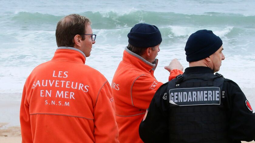 A French gendarme, right, and rescue workers chat during searches for the chief executive of sportsw