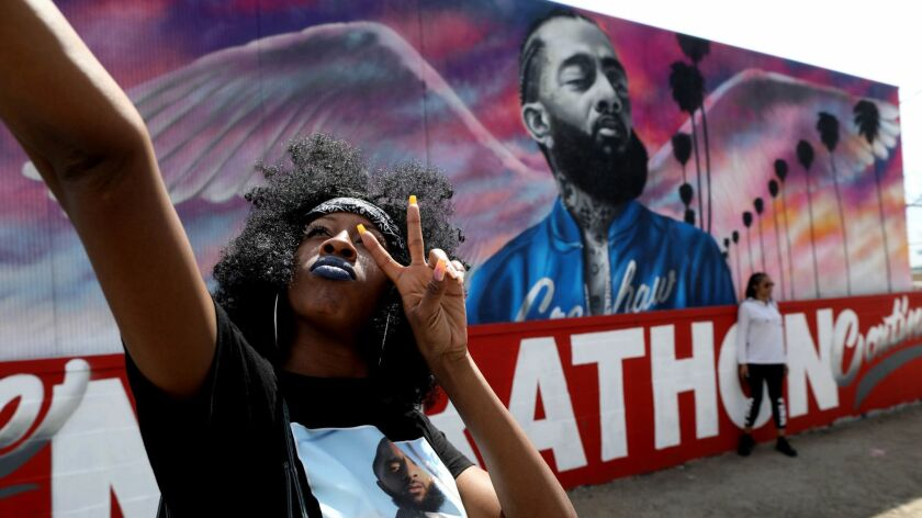 LOS ANGELES, CALIF. -- THURSDAY, APRIL 11, 2019: Cindy Lynn, of Los Angeles, with a mural of Nipsey