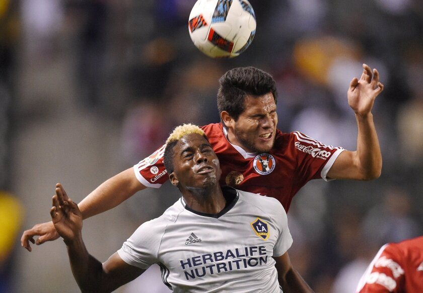 Los Angeles Galaxy forward Gyasi Zardes, left, tries to head the ball along with Club Tijuana defender Hiram Munoz during the first half of a soccer match, Tuesday, Feb. 9, 2016, in Carson, Calif. (AP Photo/Mark J. Terrill)