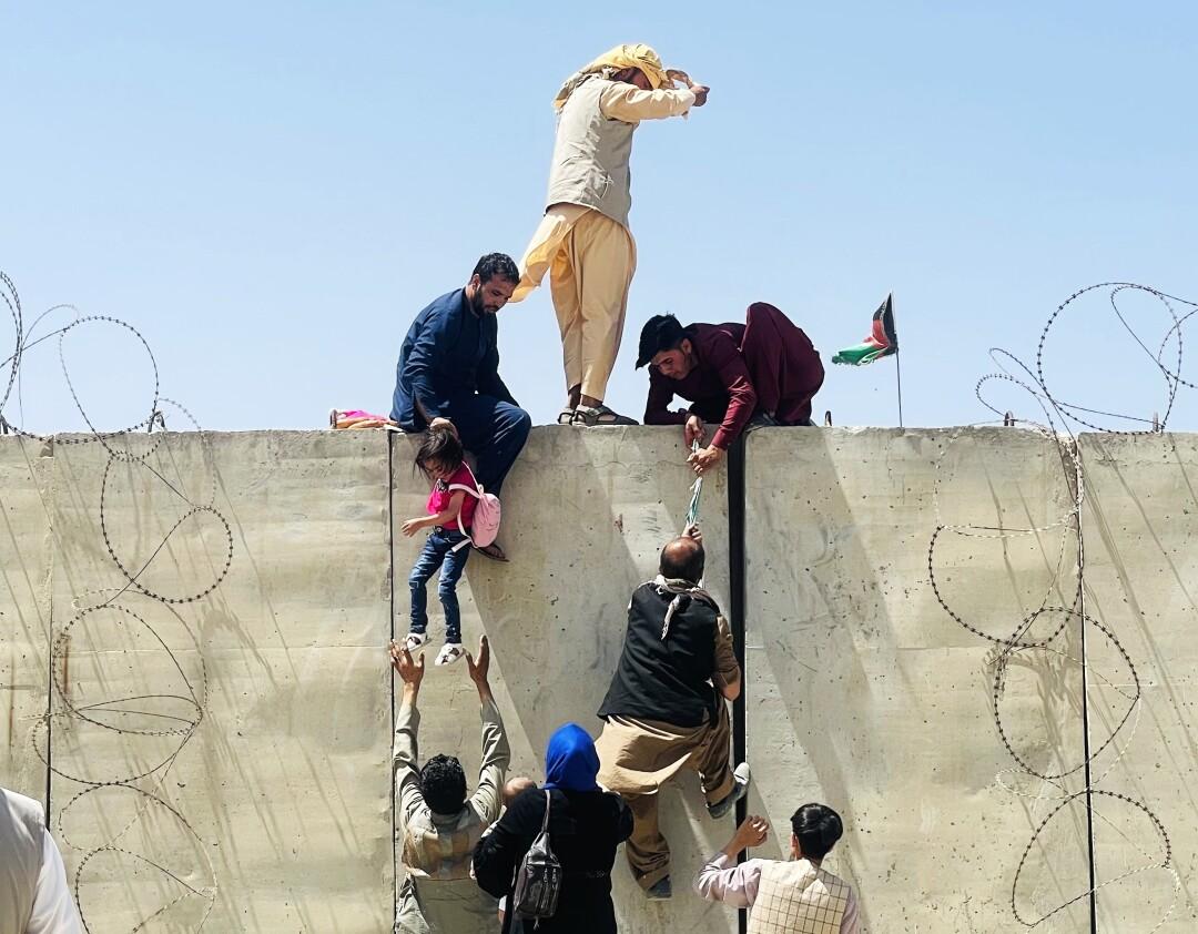 Afghans climb over a tall barrier