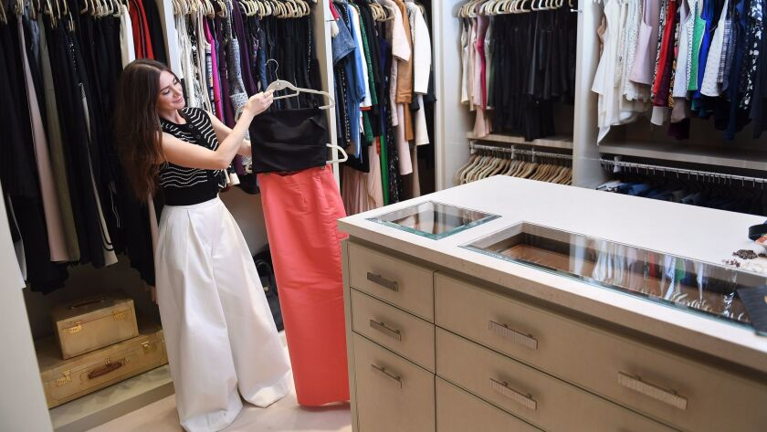 Rochelle Gores Fredston shows some of the designer pieces that stock her closet.