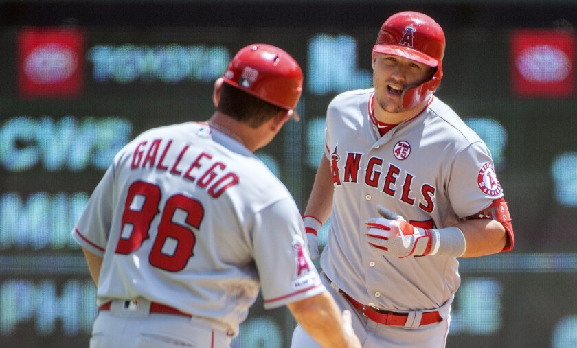 ngels slugger Mike Trout is congratulated by third base coach Mike Gallego.