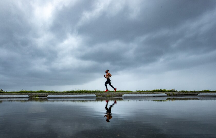 A jogger runs along the path at Will Rogers State Beach as storm clouds move onshore in Pacific Palisades earlier this month.