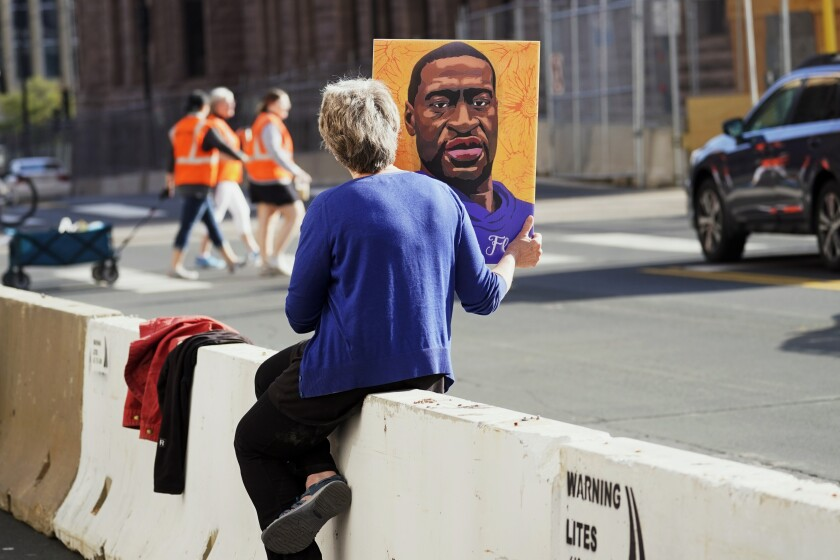 A woman holds a George Floyd picture while seated on a concrete barrier
