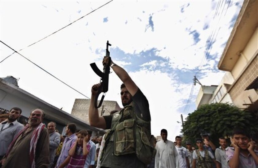 A Syrian gunman shoots in the air during the funeral of 29 year-old Free Syrian Army fighter, Husain Al-Ali, who was killed during clashes in Aleppo, in the town of Marea on the outskirts of Aleppo city, Syria, Thursday, Aug. 9, 2012. (AP Photo/ Khalil Hamra)