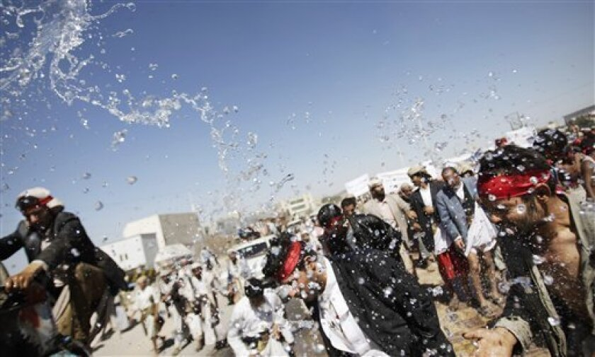 Protestors are sprayed with water to cool off during the fifth day of a five-day march from the impoverished Red Sea city of Hudaydah to Sanaa demanding the prosecution of Yemen's President Ali Abdullah Saleh in Sanaa, Yemen, Sunday, Jan. 8, 2012. (AP Photo/Hani Mohammed)