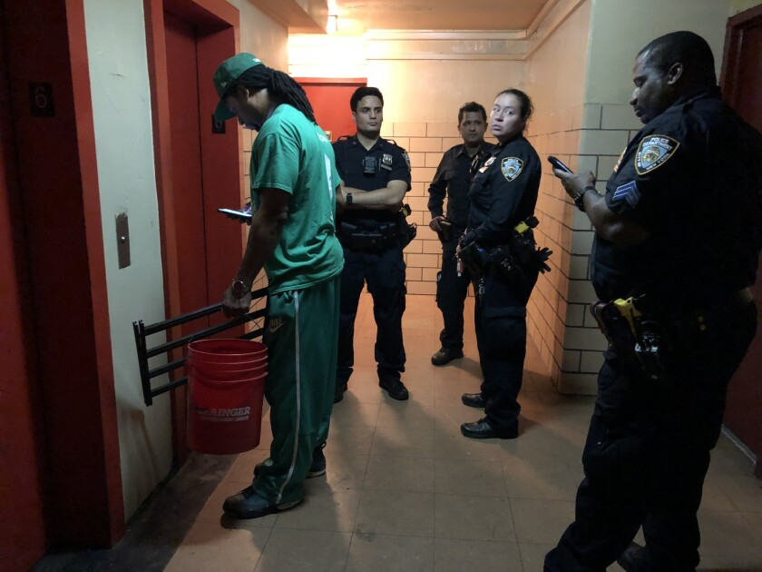 NYPD stand outside the door of the apratment where a young girl fell out of her sixth-floor window on Monday.