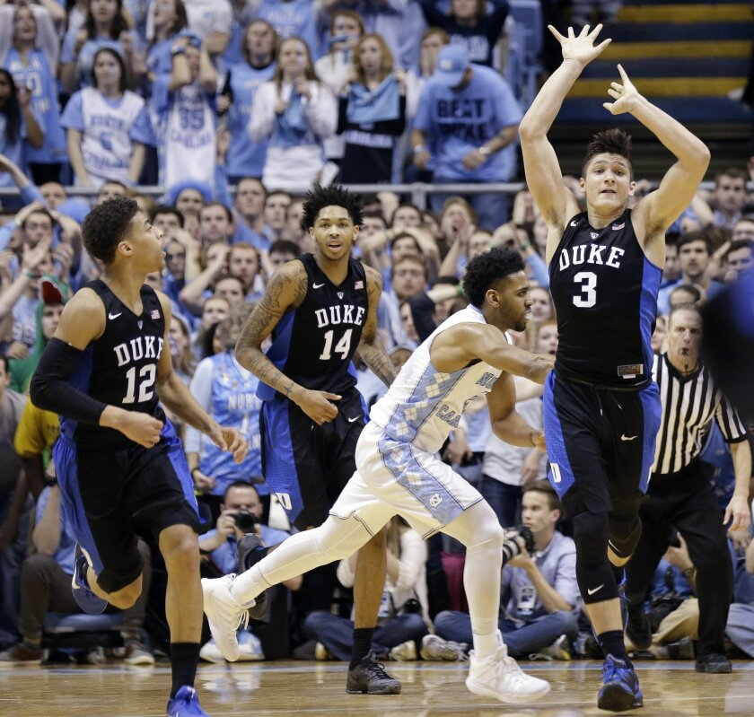 Duke's Derryck Thornton (12), Brandon Ingram (14) and Grayson Allen (3) react as time expires while North Carolina's Joel Berry II runs off of the court following an NCAA college basketball game in Chapel Hill, N.C., Wednesday, Feb. 17, 2016. Duke won 74-73. (AP Photo/Gerry Broome)