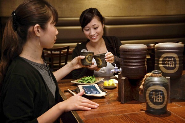 Midori Hasegawa, left, and Ryoko Yanai demonstrate the maewari, a formal shochu service, similar to a tea ceremony. A large, inverted ceramic bottle comes to the table cradled in a stand at Yuzu in Torrance.