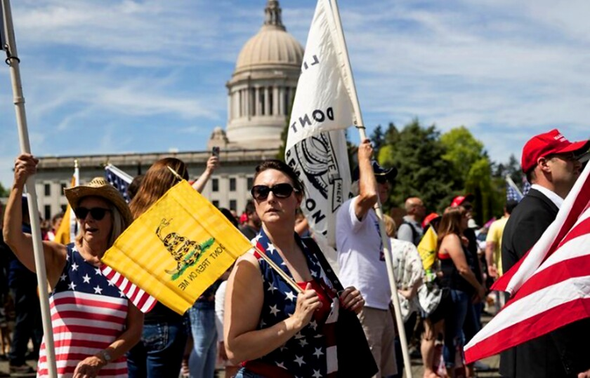 Tammy Snider, of Parkland, Wash., was one of an estimated 1,500 protesters at a rally in Olympia on Saturday against Washington state's stay-at-home order in response to the COVID-19 pandemic. Some far-right groups have allied themselves with the movement to advance their agendas.