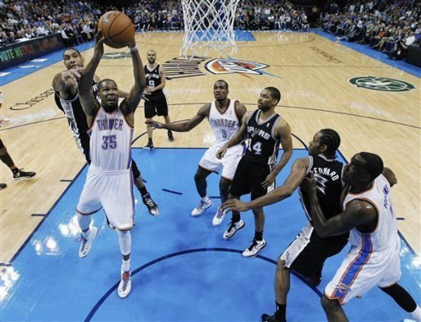 Oklahoma City Thunder forward Kevin Durant (35) shoots between San Antonio Spurs forward Tim Duncan, left, and guard Gary Neal (14) in the second quarter of an NBA basketball game in Oklahoma City, Thursday, April 4, 2013. (AP Photo/Sue Ogrocki)