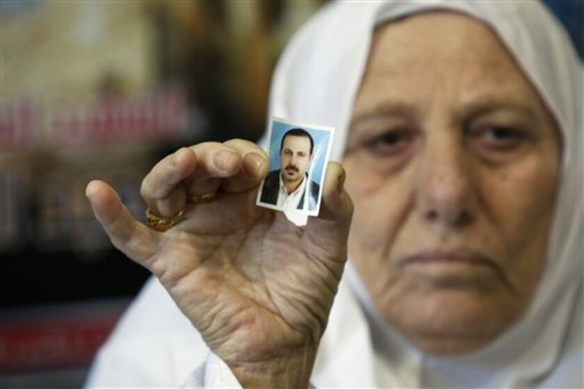 The mother of Palestinian militant Mahmoud al-Mabhouh, who was recently killed, holds up a photo of him at their home in the Jebaliya refugee camp, northern Gaza Strip, Friday, Jan. 29, 2010. Hamas claimed on Friday that Israeli agents assassinated one of the Palestinian militant group's veteran operatives in a killing allegedly carried out last week in Dubai, and vowed to retaliate. (AP Photo/Hatem Moussa)