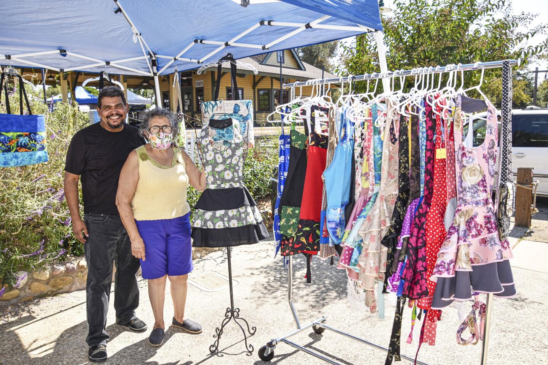 Tony Villaman and his mother, Cecilia Villaman, selling Cecilia's hand sewn aprons, dresses and blouses.