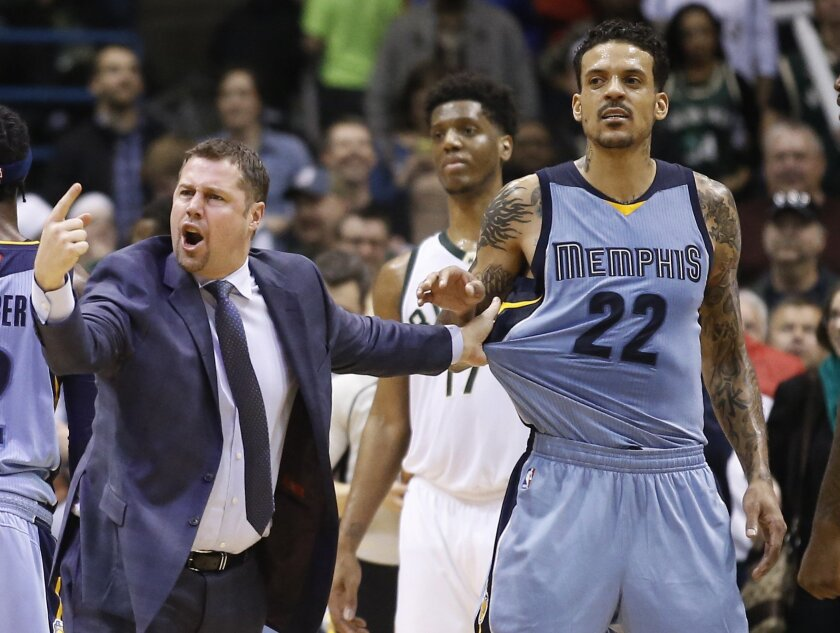 Memphis Grizzlies head coach David Joerger holds back Matt Barnes (22) after a double technical was called on Joerger and Milwaukee Bucks' John Henson during the second half of an NBA basketball game Thursday, March 17, 2016, in Milwaukee. The Bucks won 96-86. (AP Photo/Morry Gash)