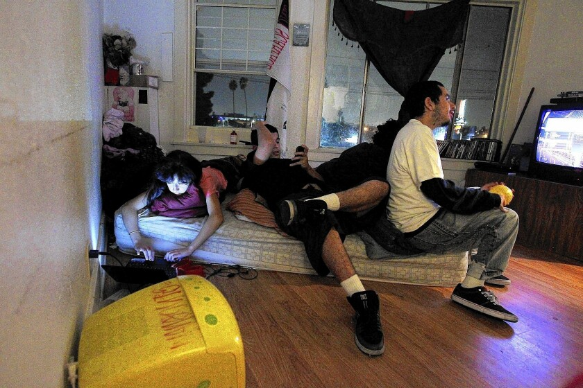 Sixteen-year-old Monica, left, plays solitaire on a laptop as her brothers Cesar and Jonathan watch TV in the tiny apartment they share with four additional family members. Stretches of Los Angeles and Orange counties have some of the most crowded housing in the country.