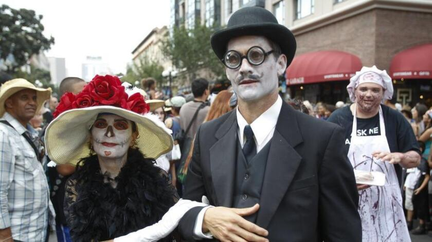 Amanda and Richard Ligato walk with other zombies on Fifth Avenue. (Hayne Palmour IV / UT San Diego)