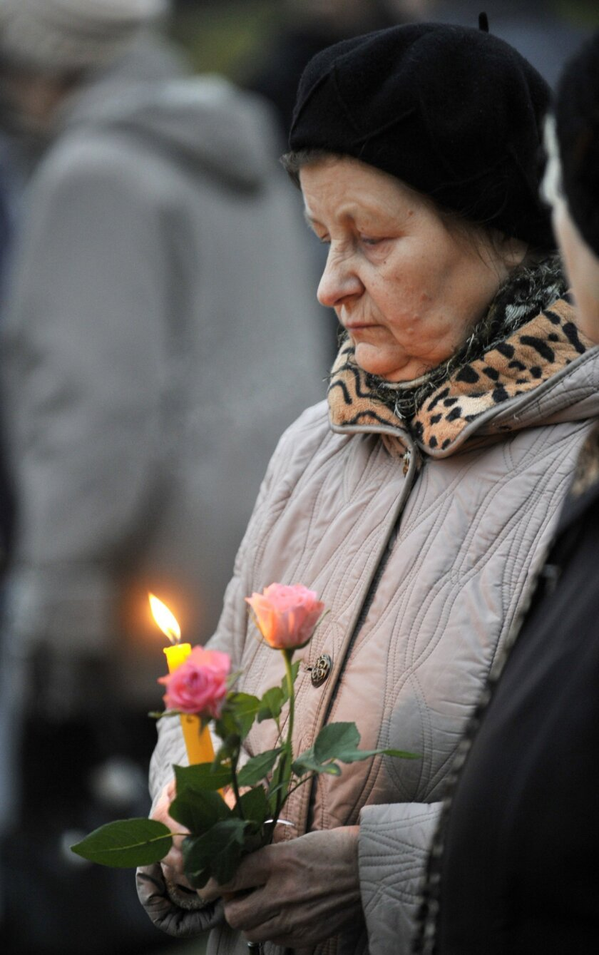 A woman holds a candles and flowers outside the collapsed Maxima supermarket in Riga, Latvia, Friday, Nov. 22, 2013. The reason for the collapse during shopping rush-hour Thursday was still not known but rescue and police officials said that possible theories include building's design flaws and poo
