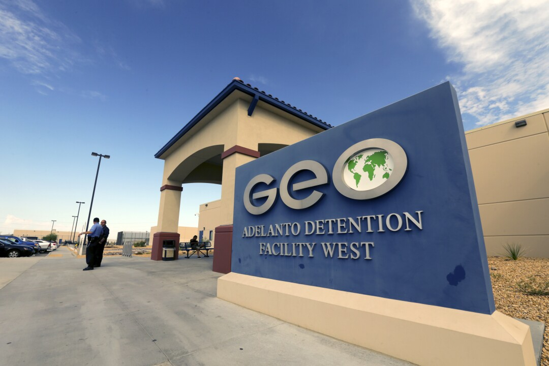 A blue sign that reads GEO Adelanto Detention Facility West outside a building