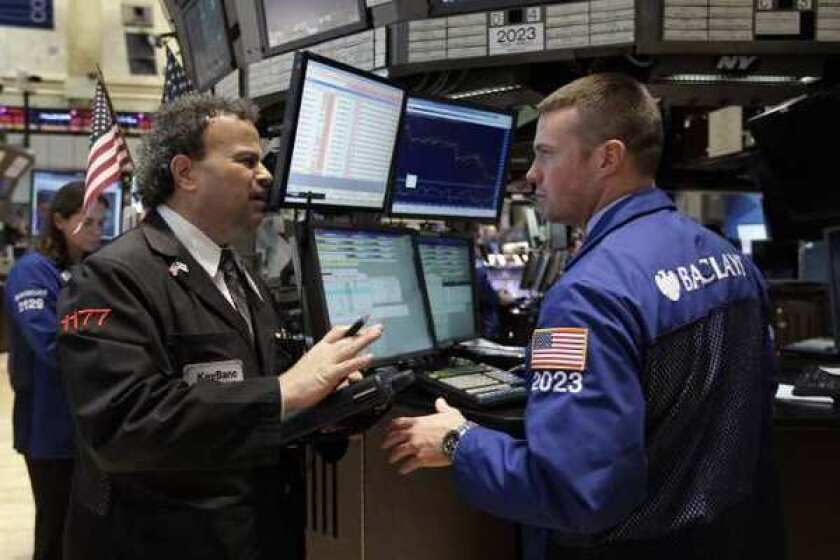 Traders work on the floor of the New York Stock Exchange. Stocks remain reasonable priced despite this year's rally.