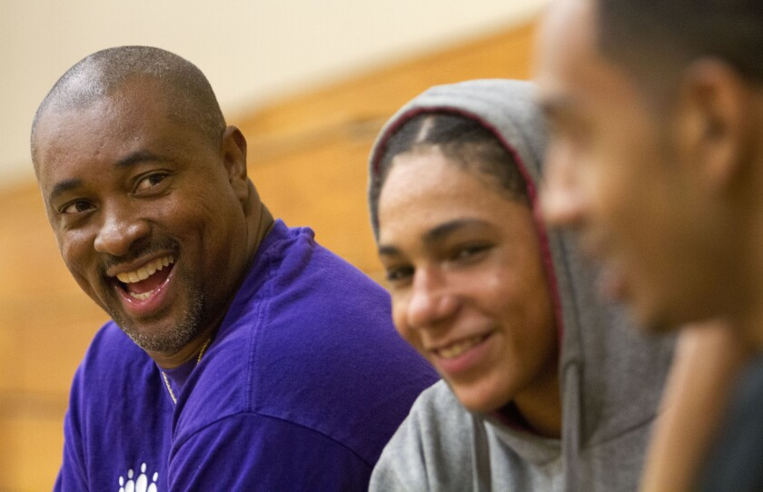 Lincoln High Basketball Coach Jeff Harper-Lewis laughs with young people at a summer basketball program.