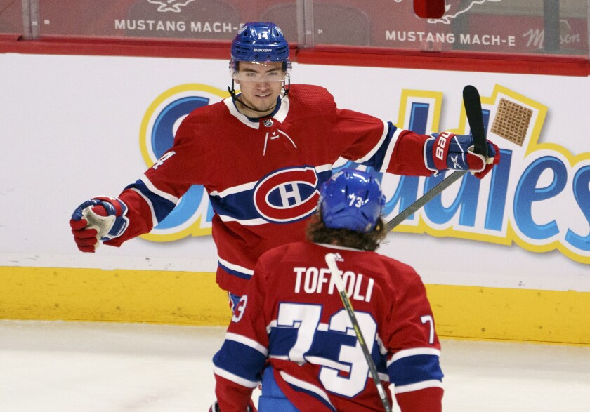 Montreal Canadiens' Nick Suzuki celebrates his goal against the Toronto Maple Leafs with teammate Tyler Toffoli during the first period of an NHL hockey game in Montreal on Monday, April 12, 2021. (Paul Chiasson/The Canadian Press via AP)