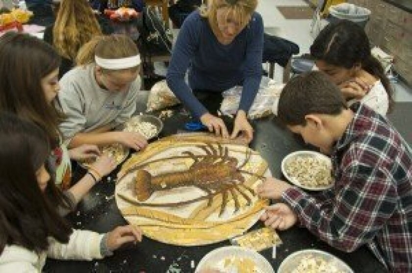 Artist Betsy Shultz (center) shows students how to piece together mosaics.