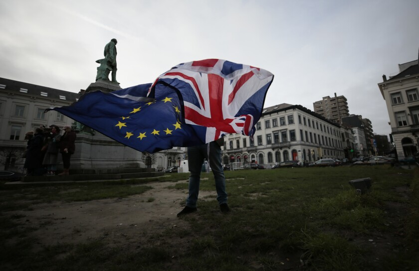 FILE - In this Thursday, Jan. 30, 2020 file photo, a man unfurls a Union and EU flag outside the European Parliament in Brussels. When Britons voted for Brexit in 2016, they were promised a smooth transition to a new economic relationship with the European Union. Now the two sides are hurtling toward a tumultuous split that threatens billions worth of trade and hundreds of thousands of jobs. (AP Photo/Virginia Mayo, File)
