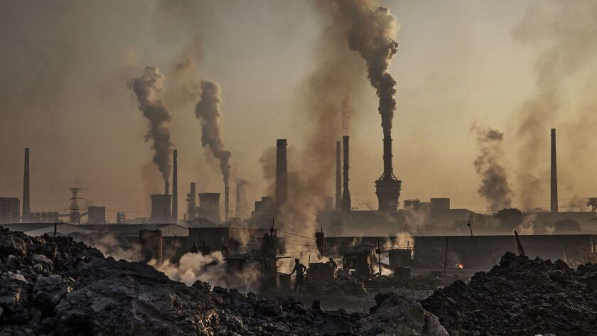 In this November 2016 photo, smoke billows from a large steel plant in Inner Mongolia, China. Chinese authorities are pushing to shut down privately owned steel, coal and other high-polluting factories scattered across rural areas.