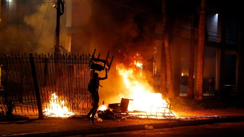 A fire is set outside the Congress building in Asuncion, Paraguay, during clashes between police and protesters opposing a constitutional amendment that would allow the election of a president to a second term.