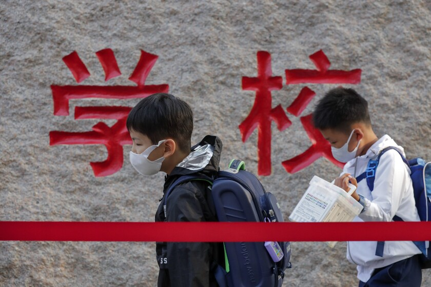 ARCHIVO - En esta fotografía del 7 de septiembre de 2020, alumnos con mascarillas para protegerse del coronavirus llegan a su escuela primaria, en Beijing. (AP Foto/Andy Wong, archivo)