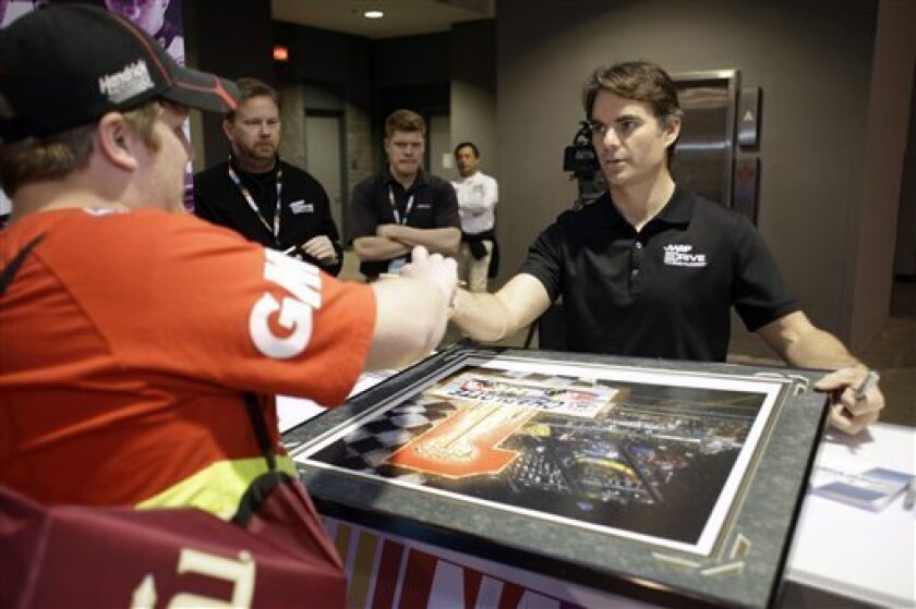 Justin McAbee, of Lyman, S.C., thanks driver Jeff Gordon for autographing his poster of Gordon winning a race at Charlotte Motor Speedway, during NASCAR Preview 2013, Saturday Feb. 9, 2013, in Charlotte, N.C. (AP Photo/Bob Leverone)