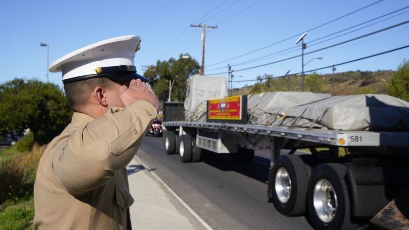 Sgt. Victor Valenzuela, from the 5th Marine Regiment at Camp Pendleton renders the hand salute as one of the trucks carrying the 5th Marines Vietnam War Memorial monument is transported on base.
