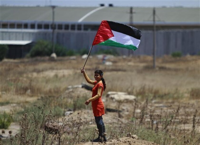 """A Palestinian girl holding a national flag stands near the border line with Israel, background, during a weekly protest march against Israel, in Beit Hanoun, northern Gaza Strip, Tuesday June 8, 2010. The sudden opening of Gaza's gateway to the world through its southern border with Egypt has turned into a scene of extreme anxiety. Hundreds crowd around border officials to snatch updates on whether they can cross to Egypt by day's end, mostly only to be told """"no."""" (AP Photo/Lefteris Pitarakis)"""