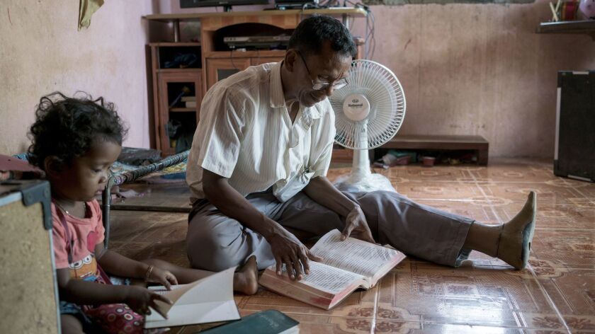 Sok Sem, 58, reads the Bible with his daughter Sok Sreypao, age 4. Sok was a commander of a special military unit of the Khmer Rouge. He committed to Christianity in 2001.
