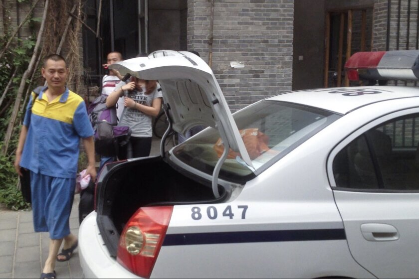In this photo taken with a mobile phone camera, Guo Jian, left, in a detention center uniform walks to a police car after he retrieved some personal belongings from his studio in Beijing Friday, June 6, 2014. The Chinese-born Australian artist detained in Beijing ahead of the 25th anniversary of the military clampdown on the student protest centered around Tiananmen Square will be deported after 15 days in custody, Australia said Friday. (AP Photo/Alexander F. Yuan)