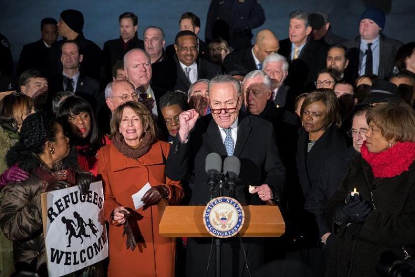 El líder del Senado de EE.UU. Chuck Schumer (c), la líder de la minoría de la Cámara de EE.UU. Nancy Pelosi (c-i) e integrantes del Senado y la Cámara participan hoy, lunes 30 de enero de 2017, en una manifestación en oposición a la prohibición de inmigración del presidente de EE.UU. Donald Trump, en frente de la Corte Suprema en Washington (Washington). EFE