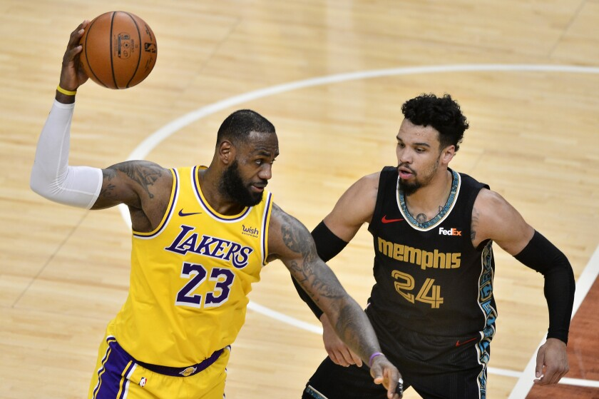 Lakers forward LeBron James catches a pass against Grizzlies guard Dillon Brooks during a game Jan. 5, 2021, in Memphis.