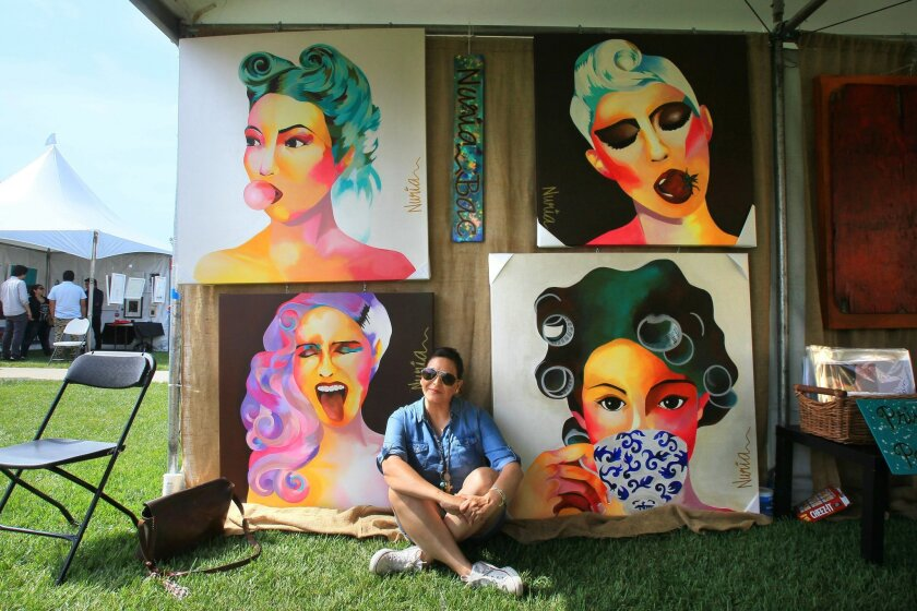Tijuana artist Nuria Bac sits in her display with some of her paintings at the Latin American Art Festival at Liberty Station.