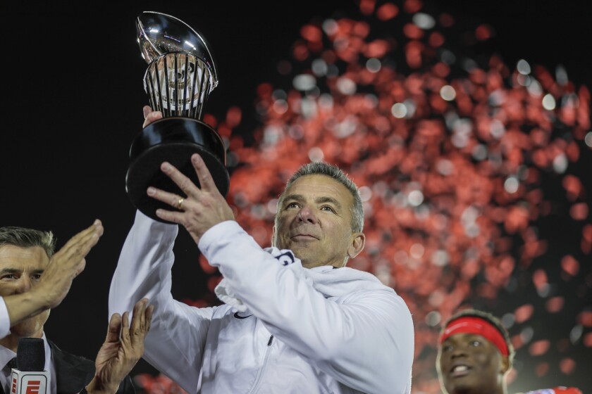 Ohio State coach Urban Meyer hoists the Rose Bowl trophy after leading the Buckeyes to a 28-23 win over the Washington Huskies in his final game.