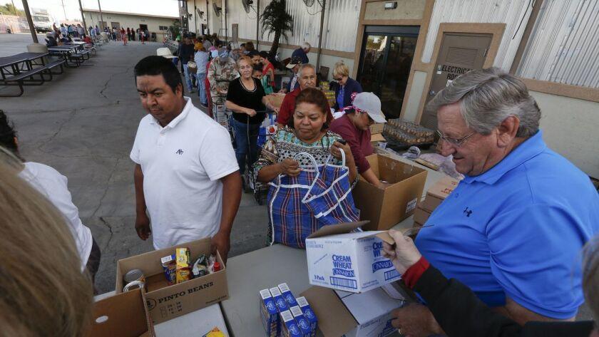 Los trabajadores agrícolas y otros residentes del Valle de Coachella esperan en fila para obtener comida gratis en La Meca, California en 2015. (Los Angeles Times)
