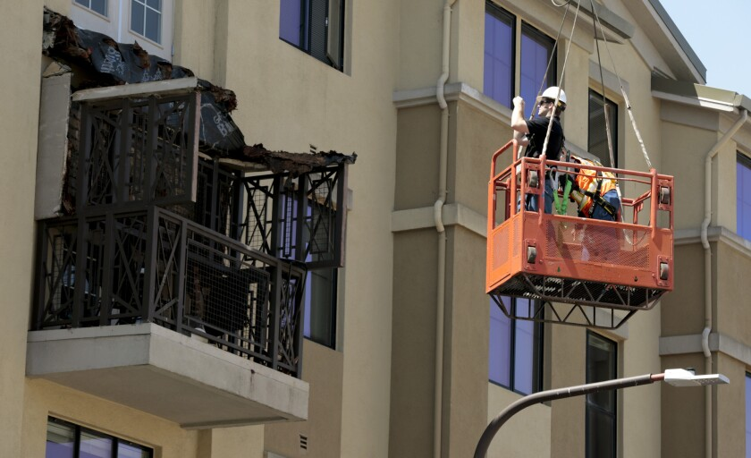 Workers examine a balcony that collapsed at an apartment building in Berkeley.