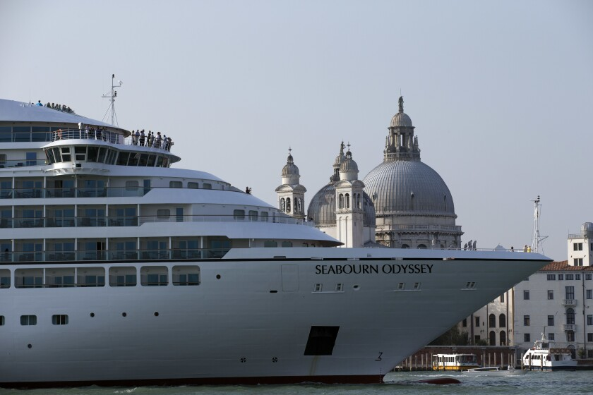 A large cruise ship with the name Seabourn Odyssey in front of domed Italian buildings in Venice