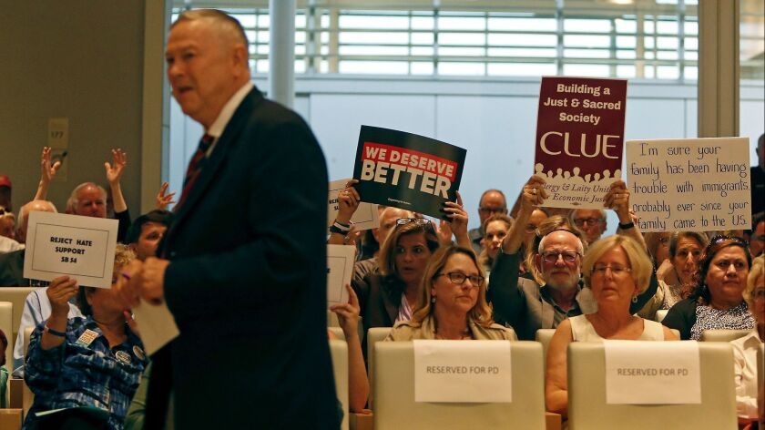 Supporters of Senate Bill 54, or the California Sanctuary State Bill, hold up signs after Rep. Dana