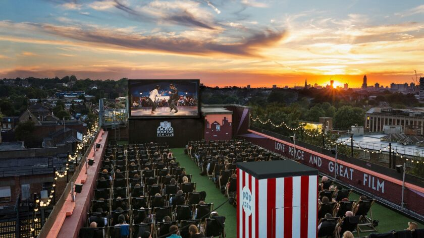 Moviegoers enjoy spectacular sunsets and great movies atop the Bussey Building at the Rooftop Cinema Club in Peckham, London. Rooftop Cinema Club is coming to San Diego on April 12.